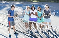 Group of mature women taking lessons from tennis instructor.